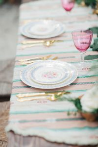 set dining table with cups and glasses. Flowers on table. Gold cutlery and beautiful rose purple colored glasses.